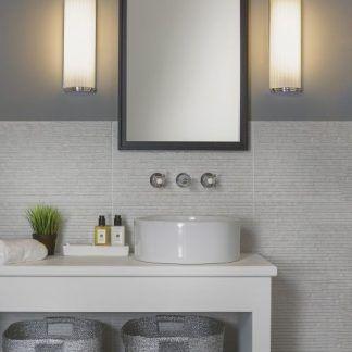 2 półokragłe kinkiety obok lustra na szarej ścianie