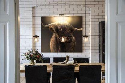 3 lampy wiszace w salonie nad stołem drewnianym