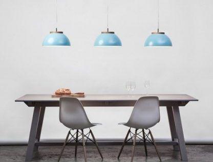 3 niebieskie lampy wiszace nad drewnianym stołem w salonie