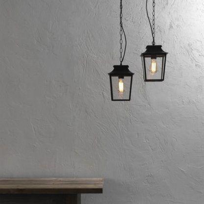 aranżacja industrialnej lampy wiszącej nad stołem w salonie