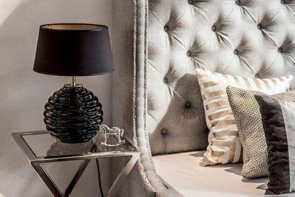 aranżacja sypialni ze szklanym stolikiem i czarną lampą stołową