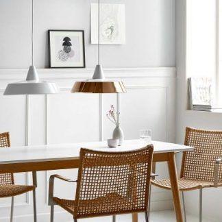 biała i miedziana lampa wisząca nad stołem w jadalni