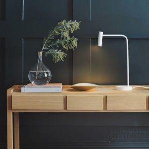 biała lampa biurkowa na granatowej ścianie