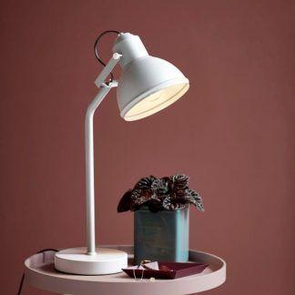 Biała lampa na stoliku w bordowej aranżacji