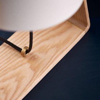biała lampa stołowa na drewnianej podstawie