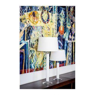 biała lampa stołowa na kolorowej grafice ściennej