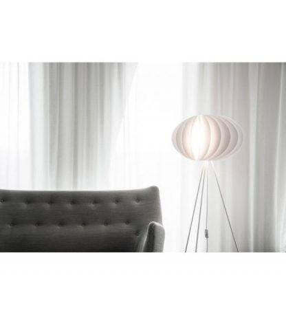biała lampa trójnog do szarej kanapy w salonie