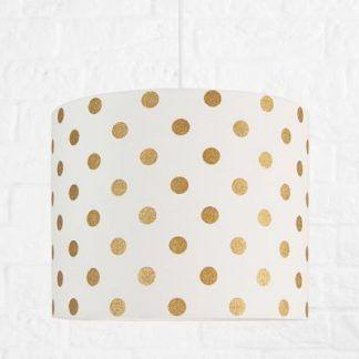 Biała lampa w złote grochy na tle betonowej ściany