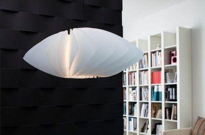 biała lampa wiszaca na czarnej ścianie