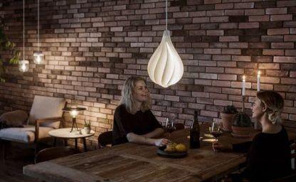 biała lampa wisząca na ścianie z czerwonej cegły