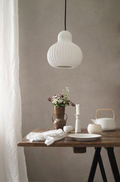 biała lampa wisząca w kształcie gruszki - do beżowej ściany