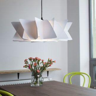 biała lampa wisząca z płatków nad brązowym stołem