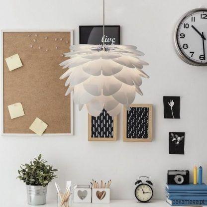 biała nowoczesna lampa wisząca obok ściany i czarnych ozdób