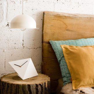 Biała okrągła lampa wisząca nad stolikiem w sypialni