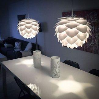białe lampy wiszące nad biały podłużny stół w salonie