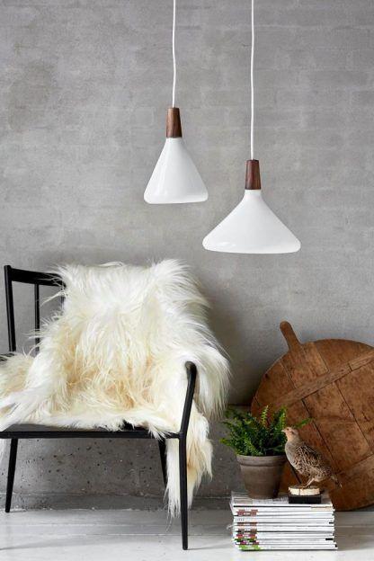 białe lampy wiszace obok krzesła na betonowej ścianie