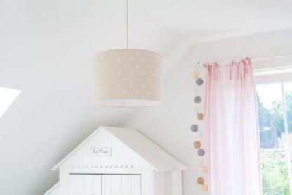 Białe ściany w pokoju z beżową lampą w białe grochy