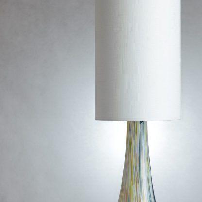 Biały abażur na szklanej podstawie w cętki do sypialni
