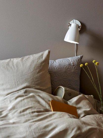 Biały kinkiet w beżowej aranżacji sypialni