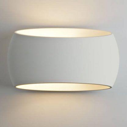 biały kinkiet z owalnym kloszem pionowe światło