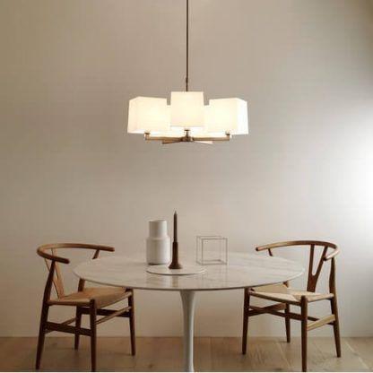 biały zyrandol z kwadratowymi abażurami nad stołem w jadalni