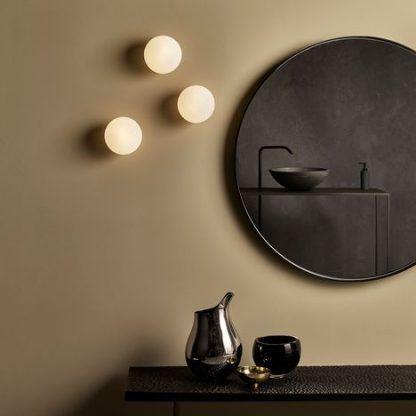Brązowa aranżacja ścian łazienki z okrągłymi kinkietami