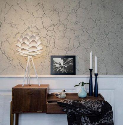 ciekawa lampa na tripodzie na drewnianej komodzie i ścianie