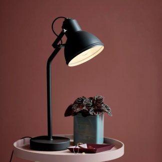 Czarna lampa na stoliku w bordowej aranżacji