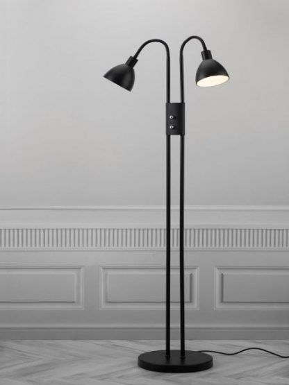 czarna lampa podłogowa z dwoma kloszami na szarej ścianie