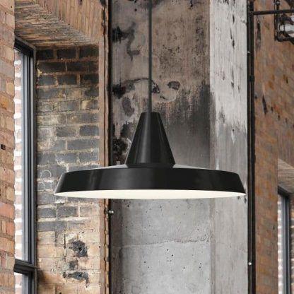 czarna lampa wisząca na tle czerwonej cegły