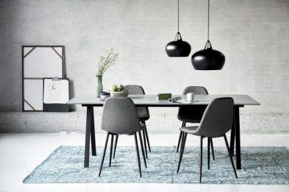 Czarna lampa wisząca nad stołem na tle betonowej ściany