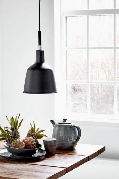 czarna skandynawska lampa wisząca nad drewniany stół w kuchni