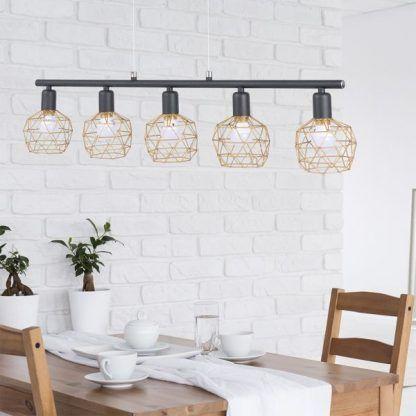 Czarna wisząca lampa ażurowymi kloszami w jadalni