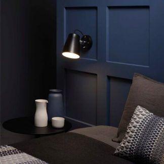 czarny kinkiet na granatowej ścianie sypialnia aranż