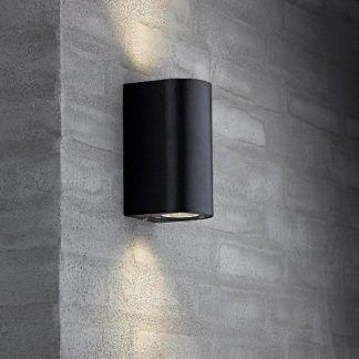 czarny kinkiet nowoczesny na ścianie z cegieł szarych