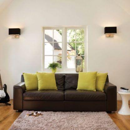 czarny kinkiet w białym wysokim salonie - aranżacja sofy
