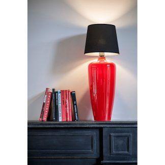 czerwona lampa stołowa na czarnej komodzie