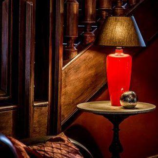 czerwona lampa stołowa z czarnym abażurem do drewna