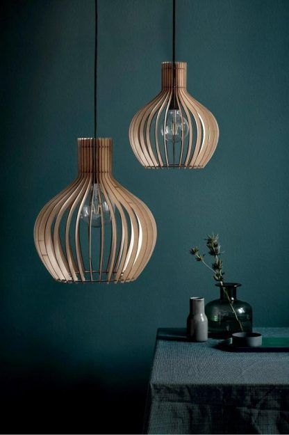 dwie drewniane lampy wiszace do ciemnej zielonej ściany w salonie