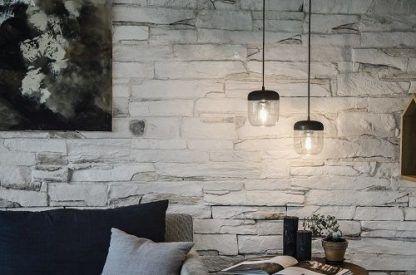 dwie lampy wiszące w salonie na ścianie z kamienia