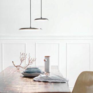 dwie srebrne lampy nad sosnowym stołem