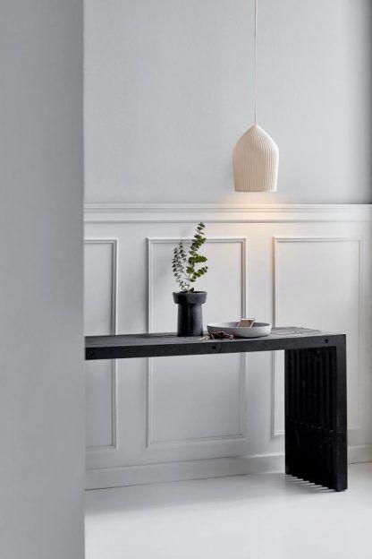 elegancka lampa wisząca do salonu nad stół obok ściany