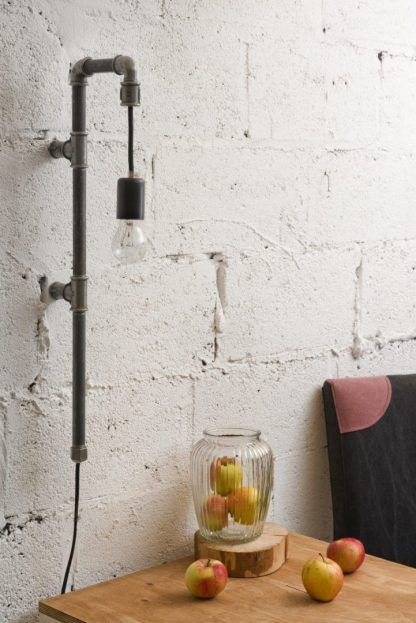 industrialna lampa z rur do ściany z białej cegły