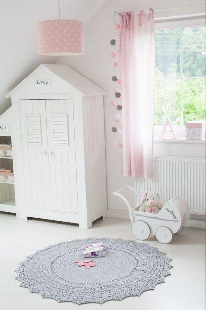 Jasne ściany pokoju z różową lampą w białe grochy