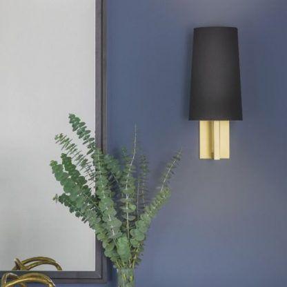 złoty kinkiet z czarnym abażurem na niebieskiej ścianie