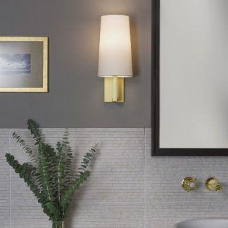 kinkiet złoty z białym abażurem do łazienki obok lustra