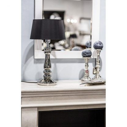srebrna lampa stołowa na tle lustra salon