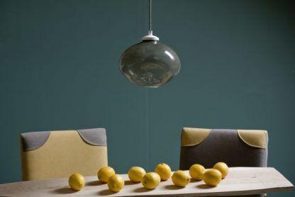 kulista lampa wisząca z szarego szkła nad stół