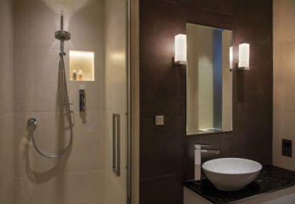 kwadratowe kinkiety do brązowej ściany w łazience