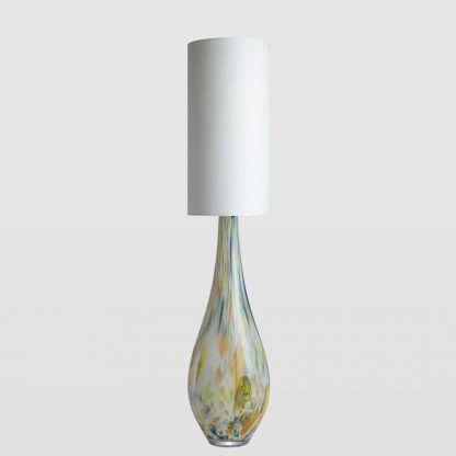 Lampa do sypialni ze szklaną podstawą w cętki i białym abażurem